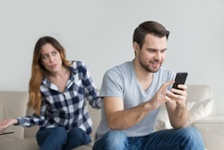 Jealous suspicious mad wife arguing with obsessed husband holding phone texting cheating on cellphone, distrustful girlfriend annoyed with boyfriend mobile addiction, distrust social media dependence