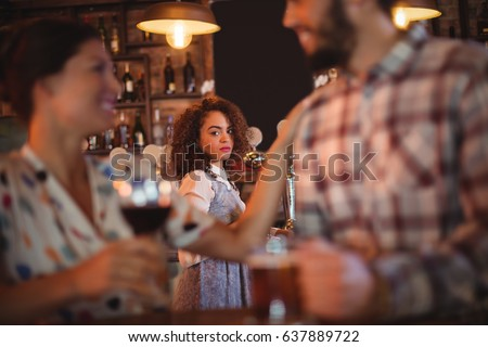Jealous woman looking at couple flirting with each other in pub