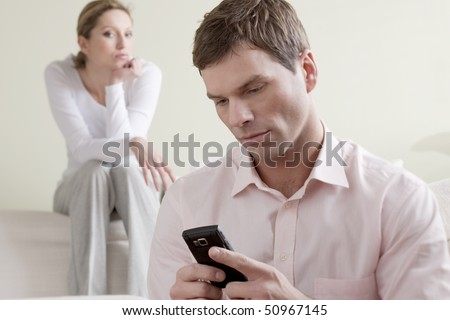 Jealous  woman looking at her partner chatting on the phone