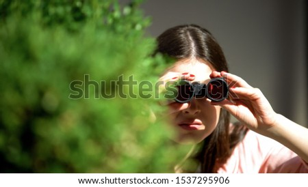 Jealous woman with binoculars hiding behind tree spying for husband, betrayal