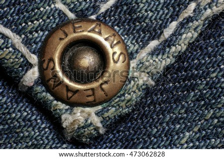 Jeans rivet, old dirty jeans, macro photo. Fashion jeans button. Sign JEANS JEANS on bronze part of button. Blue denim