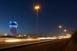 Jeddah water tower at night, with car lights motion on the street. Saudi Arabia