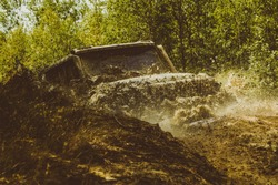 Jeep crashed into a puddle and picked up a spray of dirt. 4x4 travel trekking. Expedition offroader. Mud and water splash in off-road racing