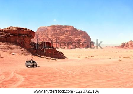 Jeep safari in Wadi Rum desert, Jordan. Tourists in the car ride on off-road on sand among the beautiful rocks