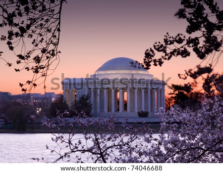 Jefferson Memorial at dawn by Tidal Basin and surrounded by pink Japanese Cherry blossoms
