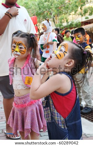 JENJAROM, MALAYSIA - CIRCA FEBRUARY 2010:Unidentified children with their face painted with tiger graffiti during the Chinese New Year event at a temple circa February 2010 in Jenjarom, Malaysia