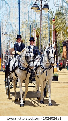 JEREZ DE LA FRONTERA, SPAIN-MAY 12:People in carriage horses walking in the royal house of the fair on the horse fair the day May 12, 2012 in Jerez de la Frontera, Spain.