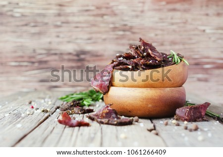 jerked dried meat, cow, deer, wild beast or biltong in wooden bowls on a rustic table, selective focus Stock photo ©