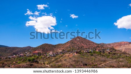 Jerome, Arizona, USA seen in the distance under bright blue skies with white clouds