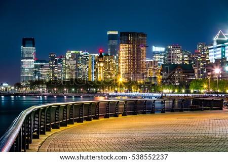 Jersey City skyline by night along Hudson river promenade.