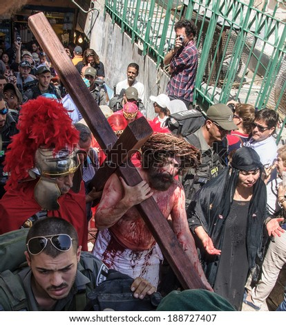 JERUSALEM - APRIL 18, 2014: A group of American actors re-enchant the crucifixion of Jesus Christ along the stations of Via Dolorosa, on Good Friday, in the old city of Jerusalem, Israel #188727407