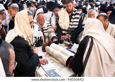 JERUSALEM - APRIL 05: A group orthodox religious Jews wearing a prayer shawl  around the Torah scroll celebrate the Jewish Pesach (Passover) at the Wailing Wall on April 05 2007 in Jerusalem.