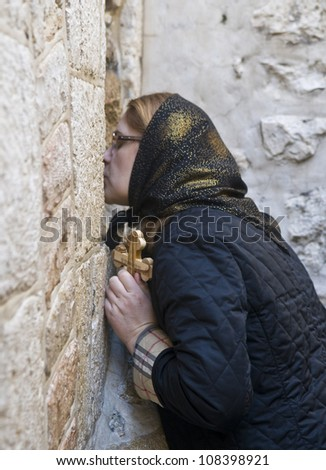 JERUSALEM - APRIL 13 : Christian pilgrim prays in the Fifth station of the Via Dolorosa during Good Friday in Jerusalem Israel on April 13 2012 - stock photo