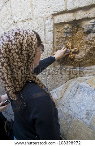 JERUSALEM - APRIL 13 : Christian pilgrim prays in the Fifth station of the Via Dolorosa during Good Friday in Jerusalem Israel on April 13 2012