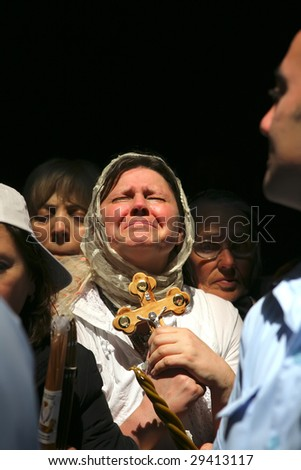 JERUSALEM - APRIL 18: Pilgrims come to Holy Sepulchre for Holy Fire (Holy Light) miracle ceremony on Holy Saturday Apr 18, 2009 in Jerusalem, Israel. About 10,000 worshipers attended the ceremony. - stock photo