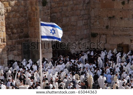 JERUSALEM - APRIL 07: The Israeli national flag fly above orthodox Jewish prayers at the Western Wall during the holiday of Passover on April 07 2008 in Jerusalem, Israel.