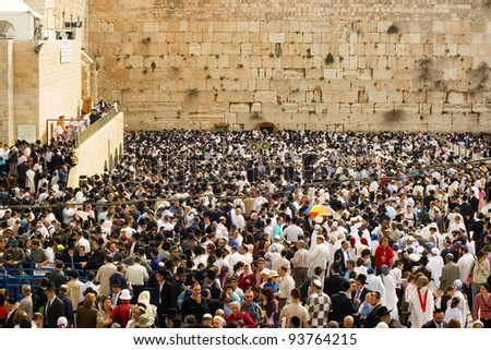 JERUSALEM - APRIL 05: The Jewish Pesach (Passover) celebration at the Wailing Wall on April 05 2007. The group of orthodox religious Jews wearing a prayer shawl draped praying around the Torah scroll