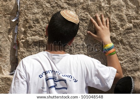 JERUSALEM - APRIL 08: The Jewish Pesach (Passover) celebration on April 08, 2012. A young religious Jewish boy prays at the Wailing Wall in the Old City of Jerusalem.