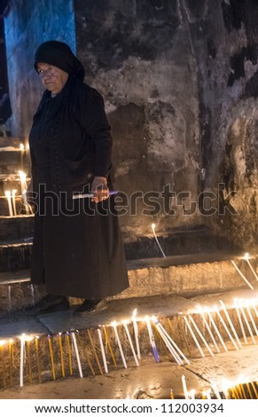 JERUSALEM - AUGUST 25 : Unidentified nun prays in the Tomb of Mary in Gethsemane during the feast of the Assumption of the Virgin Mary on August 25 2012 in old Jerusalem Israel
