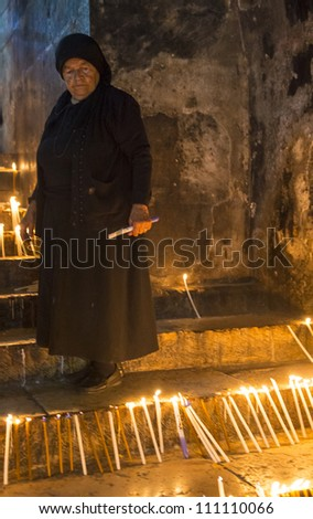 JERUSALEM - AUGUST 25: Unidentified nun prays in the Tomb of Mary in Gethsemane during the feast of the Assumption of the Virgin Mary on August 25, 2012 in old Jerusalem, Israel