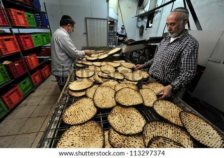 JERUSALEM ISRAEL - MARCH 16: Orthodox Jewish men prepare hand-made glat kosher matzah for Passover Jewish holiday on March 16 2010 in Jerusalem, Israel.