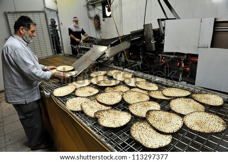 JERUSALEM ISRAEL - MARCH 16: Orthodox Jewish men prepare hand-made glat kosher matzah for Passover Jewish holiday on March 16 2010 in Jerusalem, Israel.