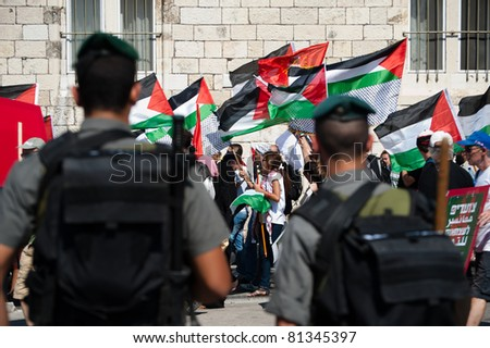 JERUSALEM - JULY 15: Israeli soldiers stand guard as thousands of Israeli, Palestinian, and international activists march in support of Palestinian rights through East Jerusalem on July 15, 2011.