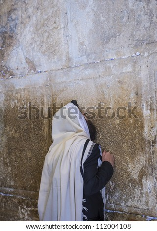JERUSALEM - JULY 29 : Jewish man prays in the Wailing wall during the Jewish holyday of Tisha B'av , on July 29 2012 in old Jerusalem , Israel