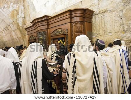 JERUSALEM - JULY 29: Jewish men prays in the Wailing wall during the Jewish holy day of Tisha B'av, on July 29, 2012 in old Jerusalem, Israel - stock photo