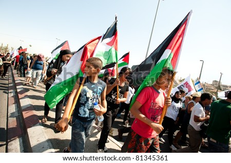 JERUSALEM - JULY 15: Palestinian children march with thousands of Israeli, Palestinian, and international activists in support of Palestinian rights through East Jerusalem on July 15, 2011.