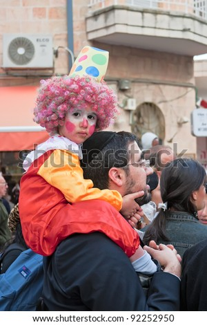 JERUSALEM - MARCH 15: Purim carnival March 15, 2006 in Jerusalem. Unidentified people watch the show. On the man's shoulders sits an unidentified child dressed like a clown