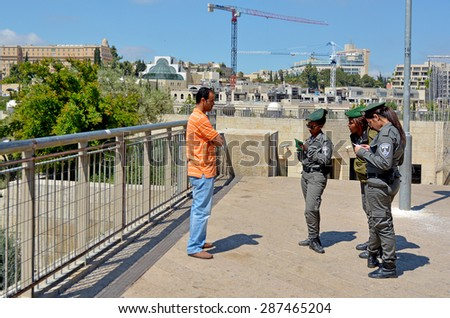 JERUSALEM - MAY 05 2015:Israeli border patrol policewomen checking Arab man ID and work permits.The force securing Israel borders and assisting IDF and law enforcements in the West Bank and Jerusalem.