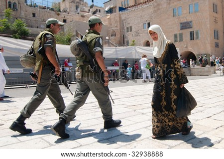 JERUSALEM - May 30: Israeli soldiers patrolling the Old City of Jerusalem cross paths with an elderly veiled Palestinian woman wearing an elaborately embroidered dress on May 30, 2009