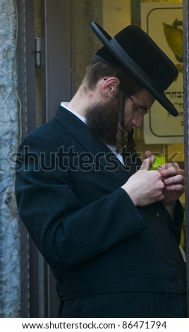 "JERUSALEM - OCT 10 : Ultra-Orthodox Jewish man inspect the ""Etrog"" in a market in Jerusalem on October 10 2011, ""Etrog"" is one of four species used during the Jewish celebration of ""Sukkot"""