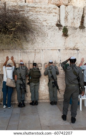 JERUSALEM - SEPTEMBER 7: Israeli security forces armed with assault rifles pray at the Western Wall in Jerusalem on September 7, 2010. Status of such holy sites is a major issue in peace negotiations.