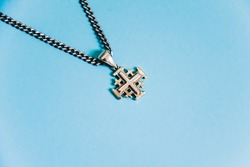 Jerusalem silver crusader cross with chain on a blue background.