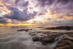 Jervis Bay sunrise with the ocean crashing onto the rocks and beach and rock pools. Colourful clouds with many hues on the horizon as the sun starts to rise