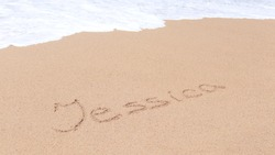 Jessica. Name in the sand The inscription of the name in the sand, washed by the wave. Creative concept.