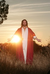 Jesus Christ backlit in sunlight with hands outstretched in blessing and clothed in his traditional red and white robe