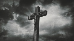 Jesus Christ crucified at Golgotha hill outside ancient Jerusalem. The crucifixion of Christ with stormy clouds in the sky. Vintage film look