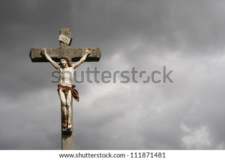 Jesus Christ crucifixion sculpture against dark clouds