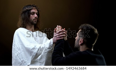 Jesus Christ holding hands of praying man, religious support, sins forgiveness