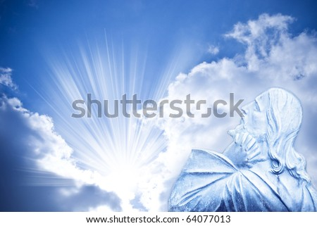Jesus Christ in praying gesture over mystical sky with divine rays of light