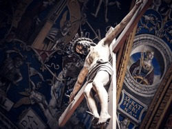 Jesus Christ nailed on a large wooden crucifix at Albi Cathedral with Renaissance frescoes of church ceiling in the background. Religious statue, Tarn department of Occitanie, France