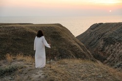 Jesus Christ on hills at sunset, back view. Space for text