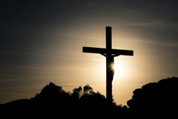 Jesus Christ on the cross silhouette at sunset - crucifixion on the Calvary Hill. Good Friday passion or Lent background.