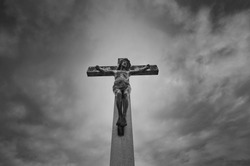 Jesus Christ on the cross standing on the light against dramatic cloudy sky, black and white