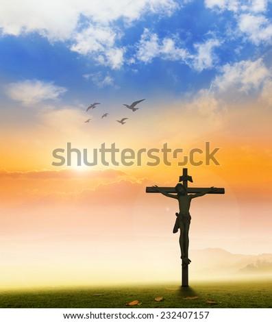 Jesus christ on the white cross over sunset background.