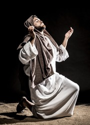 Jesus Christ praying to God consecration the bread and grapes in the dark black night. Black and white