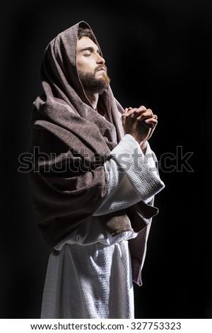 Jesus Christ praying to God in the dark black night